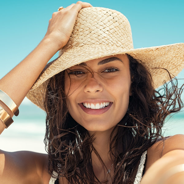 Close up face of happy young woman with straw hat with large brim at the beach enjoying her summer holidays. Portrait of beautiful latin girl relaxing at beach and looking at camera. Carefree brunette beauty woman enjoy summer days.