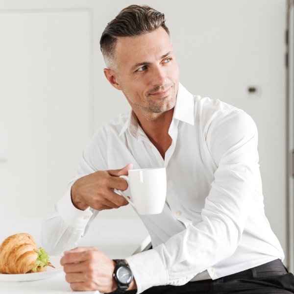 Smiling man dressed in formal clothes having breakfast while sitting on a kitchen